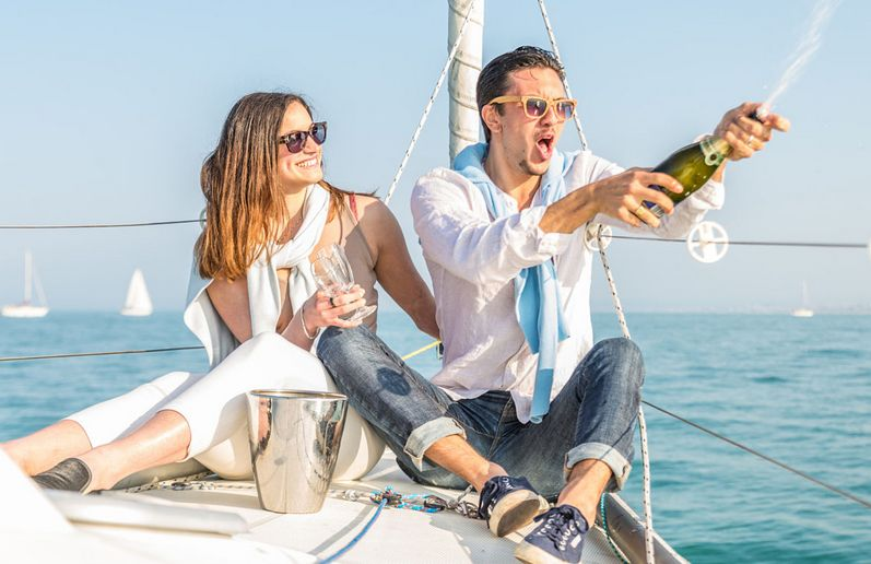 man and woman celebrating on a sailing boat